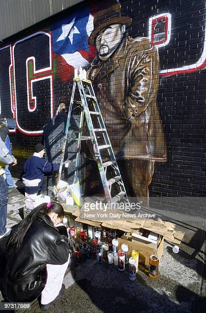 Mellissa Collazo kneels in prayer as artist puts the finishing touches on a memorial mural for the rapper Big Pun at E 163rd St and Westchester...