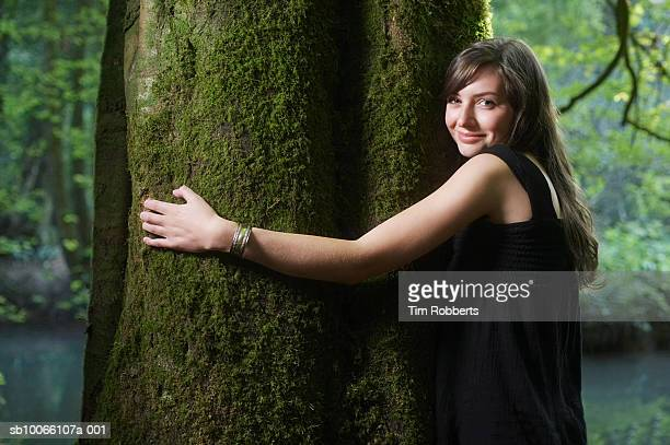UK, Mells, Somerset, young woman hugging tree in forest, portrait