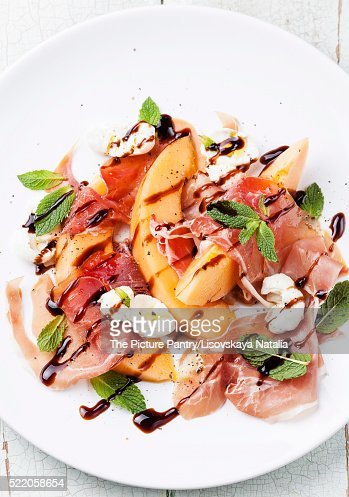 Melon and prosciutto ham salad with Mozzarella and mint leaves