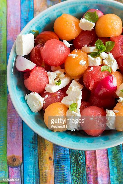 Melon salad with feta, tomato and red radish in bowl
