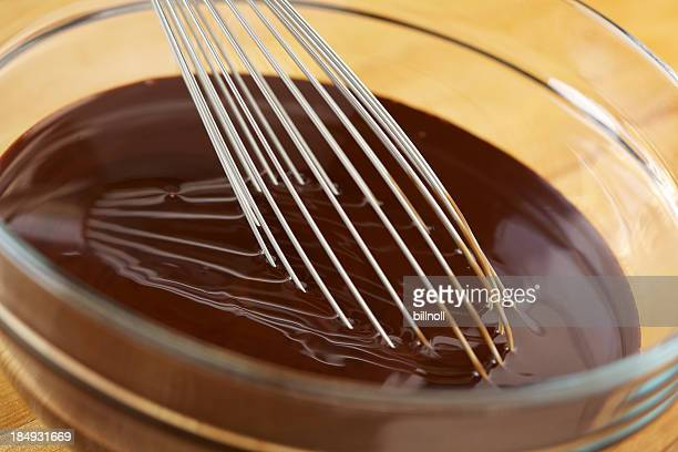 Melted chocolate with wire whisk in glass bowl