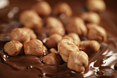 melted dark chocolate with hazelnuts, making chocolate bar, shallow focus