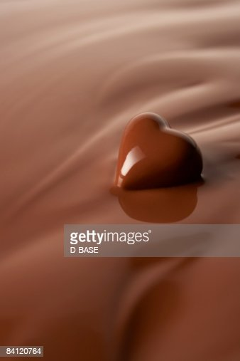 Melted heart shaped chocolate in melted chocolate : Stock Photo