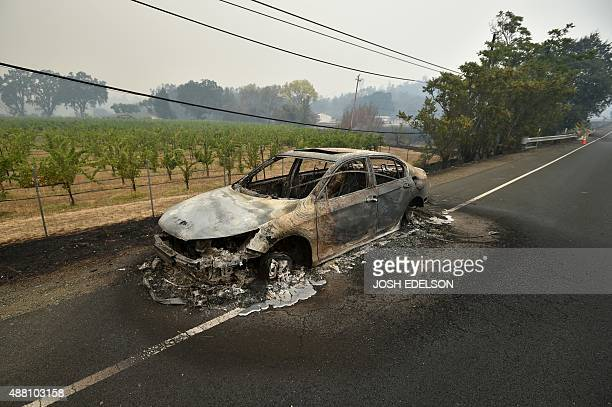 Melted metal flows from a burned out car abandoned on a highway during the Valley fire in Middletown California on September 13 2015 The governor of...