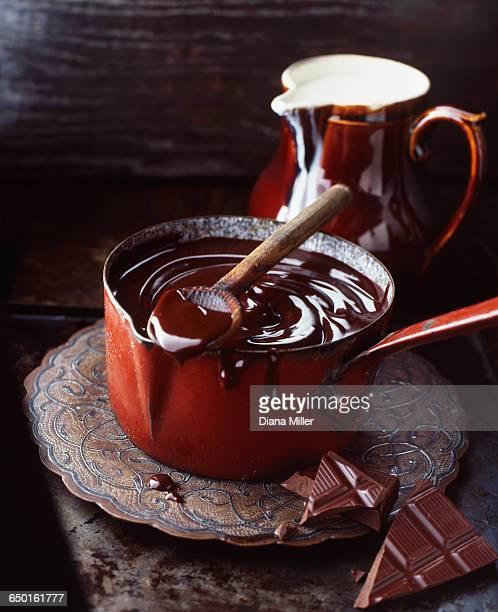 Melted milk chocolate in red vintage saucepan