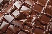 Melted pieces of dark chocolate bar in splash texture