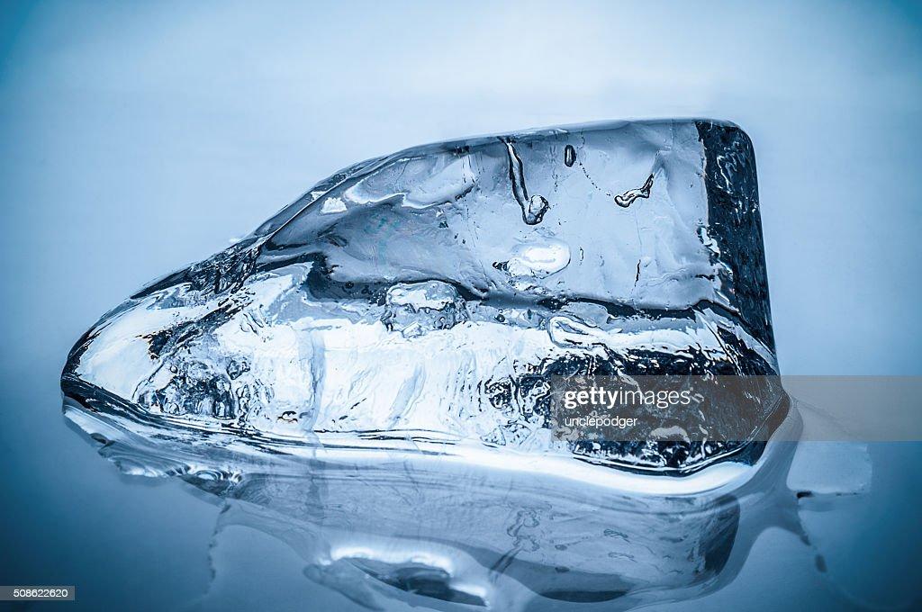 Melting ice block on blue background : Stock Photo