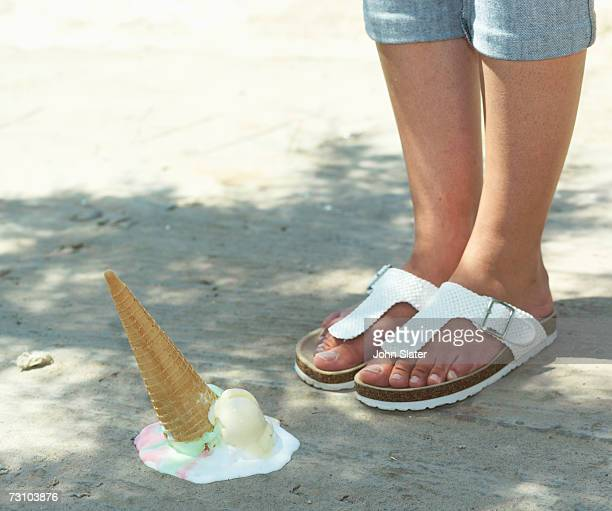 Melting ice cream cone by woman's feet, low section