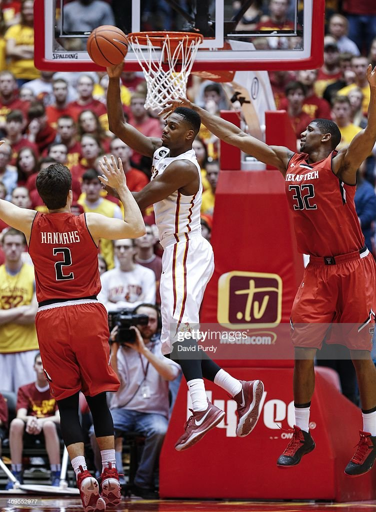Melvin Ejim #3 of the Iowa State Cyclones passes the ball as Dusty Hannahs #2 and Jordan Tolbert #32 of the Texas Tech Red Raiders puts defend in the second half of play at Hilton Coliseum on February 15, 2014 in Ames, Iowa. Iowa State defeated Texas Tech 70-64.