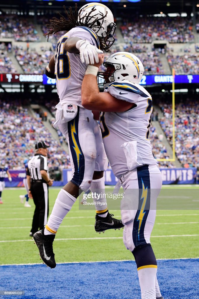 Melvin Gordon #28 of the Los Angeles Chargers is congratulated by his teammate Spencer Pulley #73 after scoring a fourth quarter touchdown against the New York Giants during an NFL game at MetLife Stadium on October 8, 2017 in East Rutherford, New Jersey.
