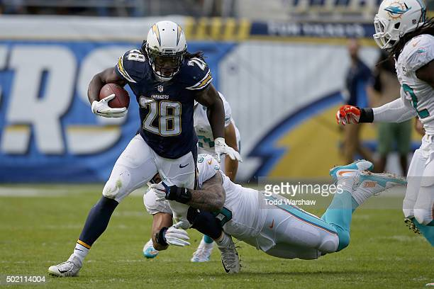 Melvin Gordon of the San Diego Chargers runs against Bobby McCain of the Miami Dolphins at Qualcomm Stadium on December 20 2015 in San Diego...