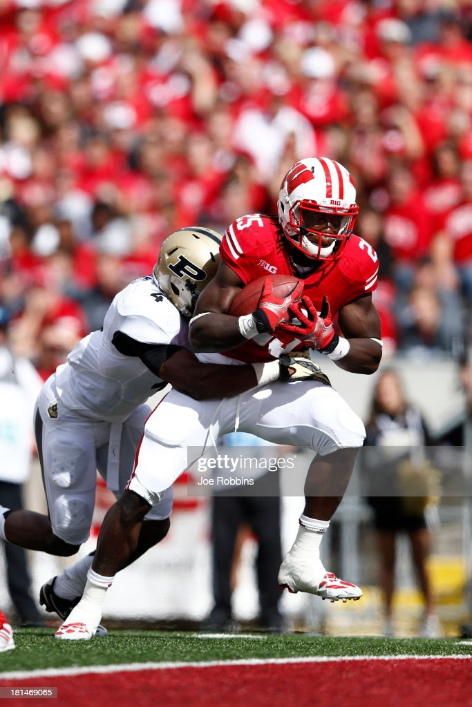 Melvin Gordon #25 of the Wisconsin Badgers carries a defender into the end zone for a five-yard touchdown in the first quarter of the game against the Purdue Boilermakers at Camp Randall Stadium on September 21, 2013 in Madison, Wisconsin.