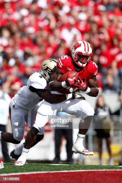 Melvin Gordon of the Wisconsin Badgers carries a defender into the end zone for a fiveyard touchdown in the first quarter of the game against the...