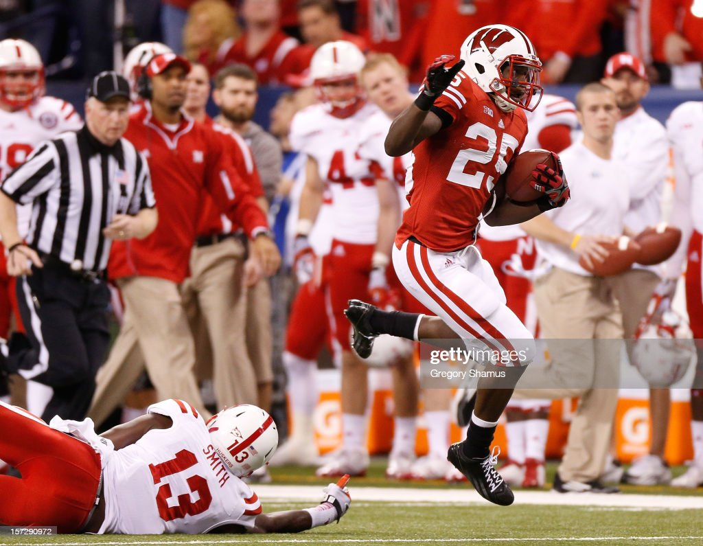 Melvin Gordon #25 of the Wisconsin Badgers escapes the tackle of P.J. Smith #13 of the Nebraska Cornhuskers for a first quarter touchdown during the Big 10 Conference Championship Game at Lucas Oil Stadium on December 1, 2012 in Indianapolis, Indiana.