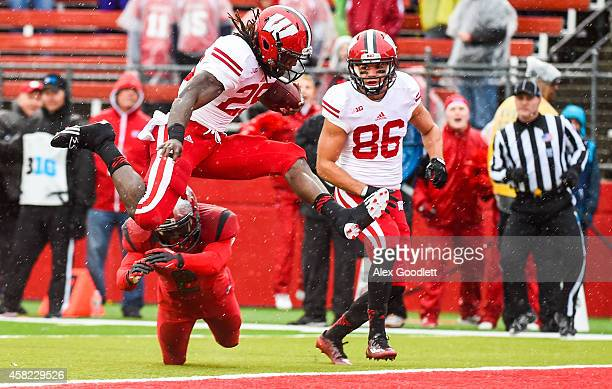 Melvin Gordon of the Wisconsin Badgers jumps over Gareef Glashen of the Rutgers Scarlet Knights to score a touchdown in the first quarter at High...