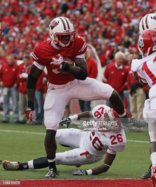 Melvin Gordon of the Wisconsin Badgers scores a touchdown as he hops over Aaron Swift of the South Dakota Coyotes at Camp Randall Stadium on...