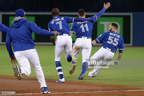 Melvin Upton Jr #7 and Kevin Pillar of the Toronto Blue Jays chase after teammate Russell Martin after the Toronto Blue Jays defeated the Texas...