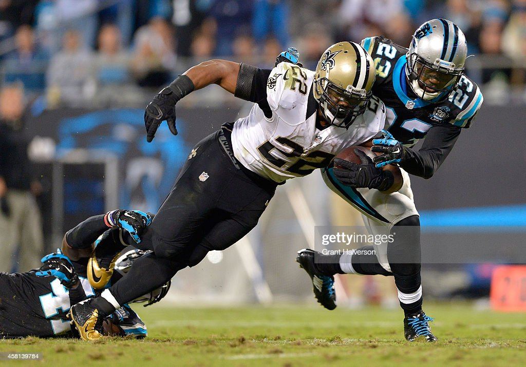 Melvin White and Roman Harper of the Carolina Panthers drag down Mark Ingram of the New Orleans Saints during their game at Bank of America Stadium...