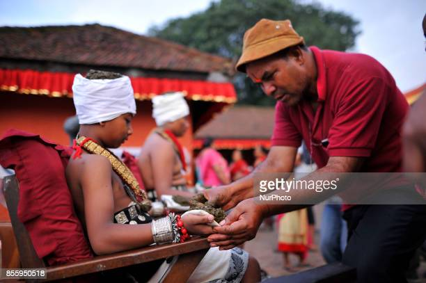 A member arranging to lit oil lamps on different parts body during the tenth day of Dashain Durga Puja Festival in Bramayani Temple Bhaktapur Nepal...