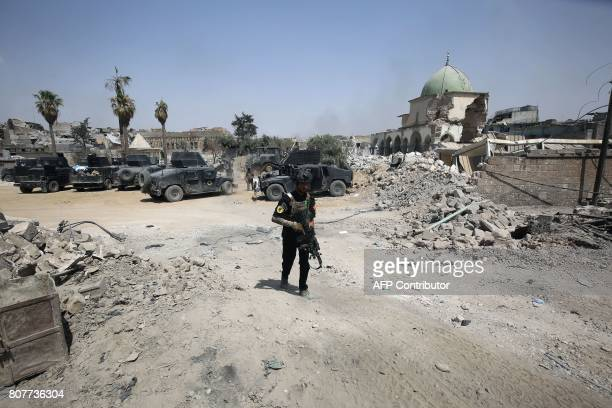 A member Iraqi CounterTerrorism Service walks down a street infront of AlNuri Mosque in Mosul's Old City on July 4 during the ongoing offensive to...