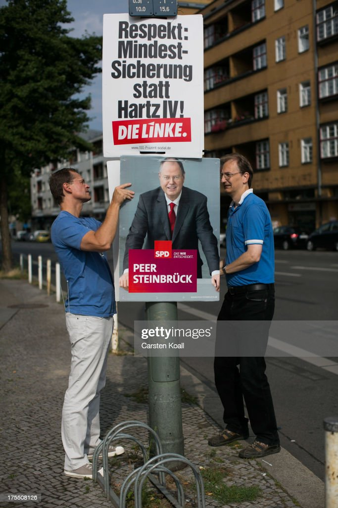 SPD- Member Michael Mueller (L), Senator for Urban Development, and Christian Heidler (R) SPD-Member since 1980, hang election campaign posters showing German Social Democrats (SPD) chancellor candidate Peer Steinbrueck on August 4, 2013 in Berlin, Germany. Germany is scheduled to hold federal elections on September 22 and so far current Chancellor Angela Merkel and her party, the German Christian Democrats (CDU), have a strong lead over the opposition.