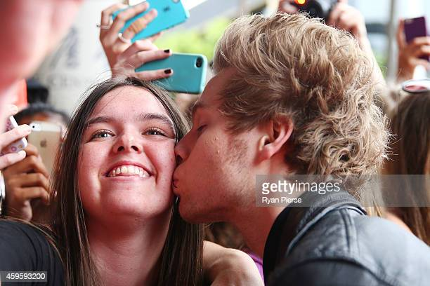 Member of 5 Seconds of Summer Luke Hemmings kisses a fan at the 28th Annual ARIA Awards 2014 at the Star on November 26 2014 in Sydney Australia