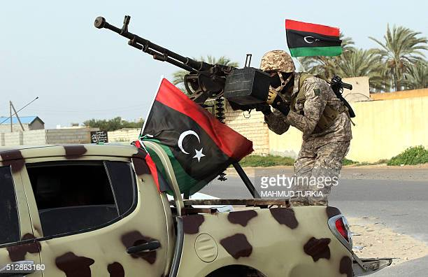 A Member of a brigade loyal to the Fajr Libya an alliance of Islamistbacked fighters stands on a pick up truck mounted with a machine gun during a...