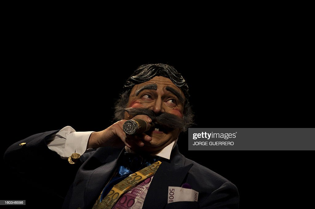 A member of a chirigota, a group that sings humorous and satirical songs during Carnival, dressed up as a banker performs 'Las verdades del banquero' (the truths of the banker) during the Carnival of Cadiz on January 29, 2013 in Cadiz, Southern Spain.