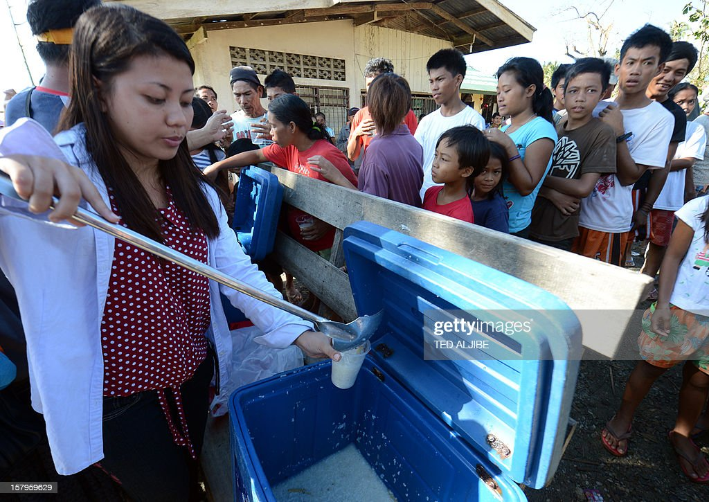 A member of a church group distributes food to displaced victims of Typhoon Bopha at an evacuation center in the town of Maparat in Compostela Valley province on December 8, 2012. Hungry and homeless typhoon survivors appealed for help on December 8 as the ravaged southern Philippines mourned its more than 500 dead and desperate people in one hard-hit town looted shops in search of food.