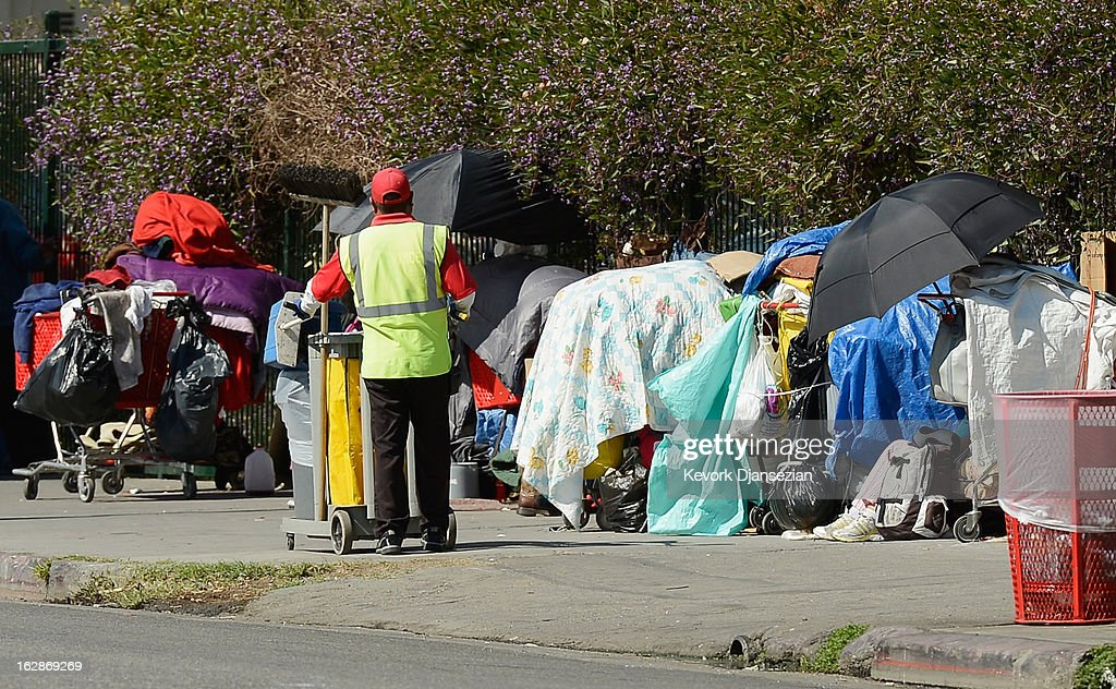 A member of a clean-up crew looks at belongings of a homeless person on a public sidewalk February 28, 2013 in downtown skid row area of Los Angeles, California. Los Angeles officials will ask U.S. Supreme Court to overturn a lower-court ruling preventing the destruction and random seizures of belongings that homeless people leave temporarily unatteneded on public sidewalks. The lower court ruling has hindered cleanup efforts.