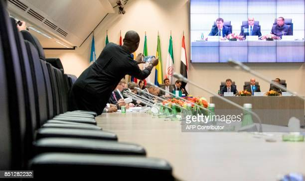 A member of a delegation takes pictures as Russian energy minister Alexander Novak speaks during the Organization of the Petroleum Exporting...