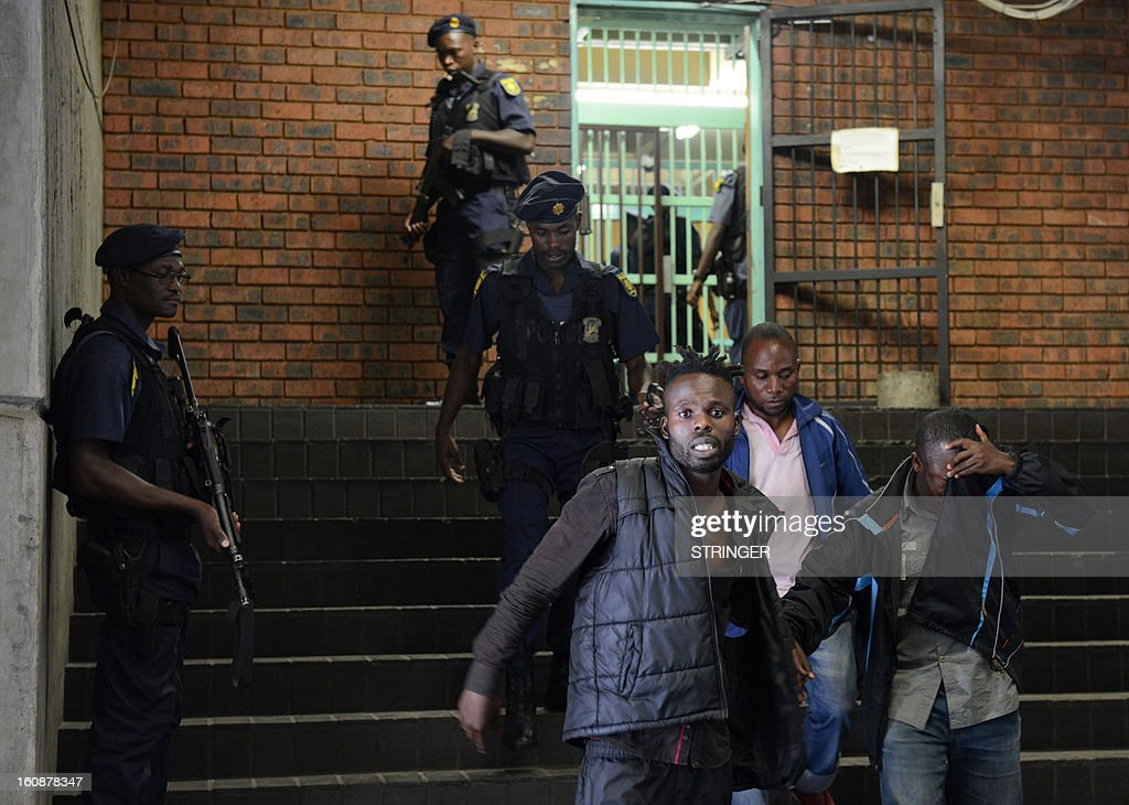 Member of a dissident organization, the Union of Nationalists for the Renewal (UNR) of the Democratic Republic of Congo, exit on February 7, 2013 after appearing in Pretoria Regional Court on charges of seeking weapons and military training to topple DR Congo President Joseph Kabila. The court on February 7 formally charged 19 DRC rebels, who were arrested on February 5 in a pre-dawn raid in a remote part of South Africa's northern and vast province of Limpopo, with plotting to stage a coup in their home country. The would-be putschists were not asked to enter pleas and were ordered to return to court on February 14.