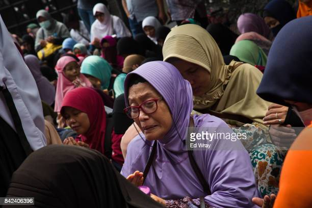 Member of a group calling themselves friends of Muslim Rohingya weeps while praying during a rally by hundreds of the women's group in front of the...