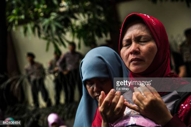 Member of a group calling themselves friends of Muslim Rohingya weeps as she prays during a rally by hundreds of the women's group in front of the...