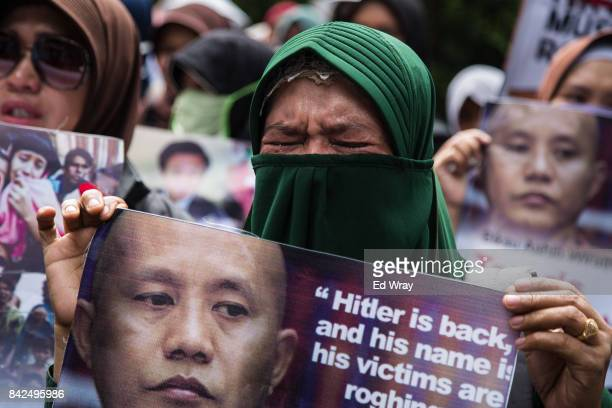 Member of a group calling themselves friends of Muslim Rohingya weeps as she listens to an account of atrocities alleged to have been committed by...