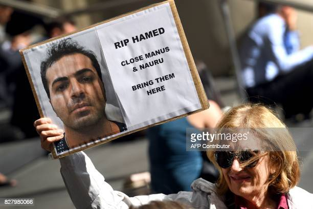 A member of a human rights group holds a placard as they call for an independent inquiry outside the Commonwealth Government offices in Sydney on...