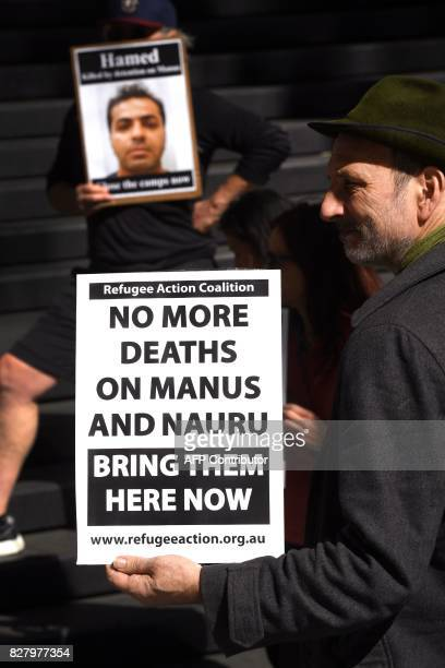 A member of a human rights groups holds a placard as they call for an independent inquiry outside the Commonwealth Government offices in Sydney on...