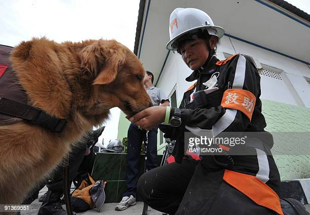 A member of a Japanese rescue team gives water to her dog in Padang West Sumatra on October 3 as they take a break from searching victims of a...