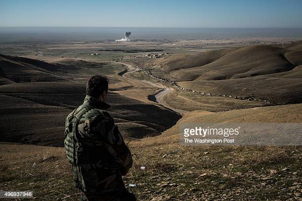 A member of a Kurdish special forces regiment watches from a hilltop as USled coalition airstrike targets a Islamic State position while a large...