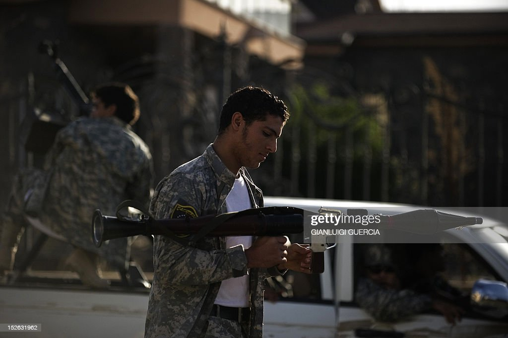 A member of a Libyan rapid unit brigade in charge of clearing unlawfully occupied buildings from militias holds his rocket-propelled grenade launcher during a patrol in Tripoli on September 23, 2012. A Libyan crackdown on lawless militias spread to the capital after armed groups that have not been integrated into state institutions were ordered to disband and evacuate their bases.