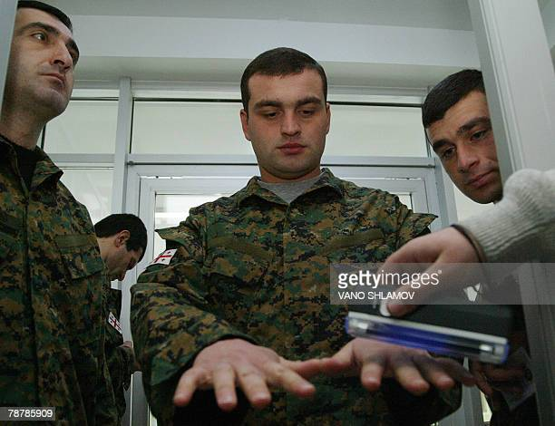 A member of a local electoral commission checks the fingers of a Georgian soldier at a polling station outside Tbilisi 05 January 2008 Georgians...