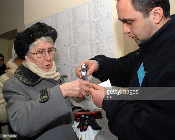 A member of a local electoral commission checks the fingers of a Georgian woman at a polling station in Tbilisi 05 January 2008 Georgians voted today...