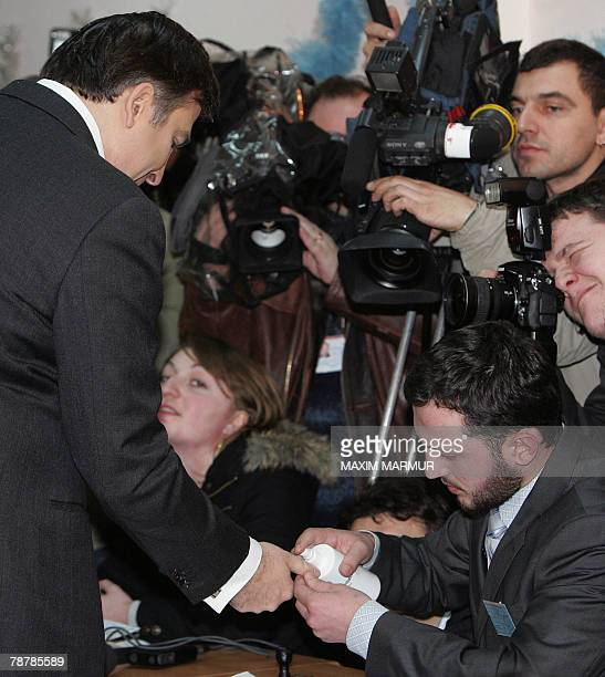 A member of a local electoral commission marks a finger of presidential candidate Mikheil Saakashvili at a polling station in Tbilisi 05 January 2008...