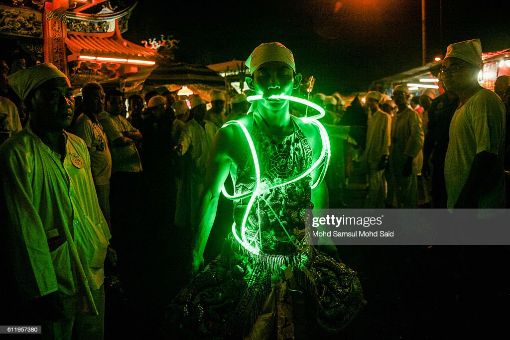 A member of a Malaysian ethnic Chinese community wait before start prayer with light at his body during the Nine Emperor Gods Festival at a temple on...