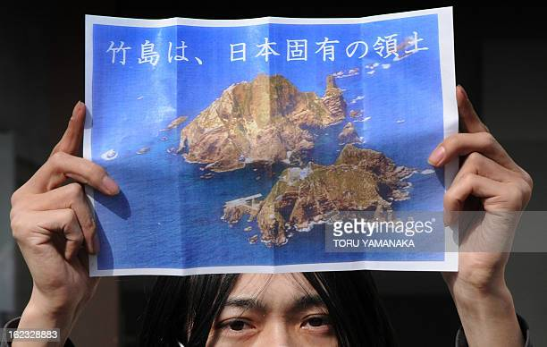 A member of a nationalist group holds a picture of a set of tiny islands in the Sea of Japan that are controlled by South Korea which are known as...