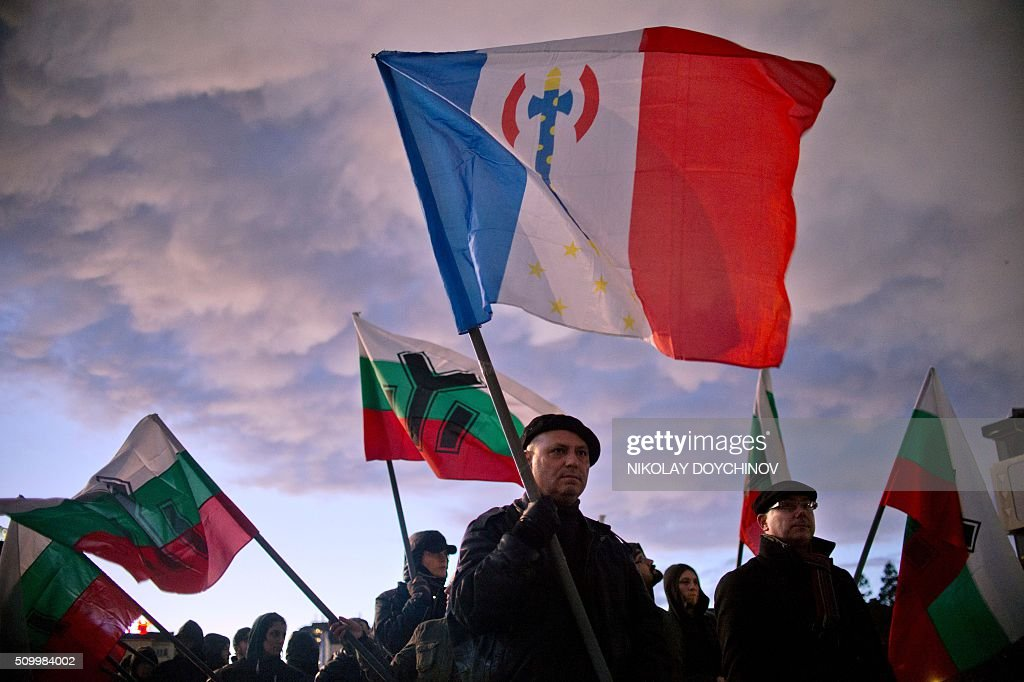 A member of a nationalist organisation holds a French flag with the emblem of the Chief of State Philippe Petain during a march in the centre of Sofia on February 13, 2016. Hundreds of Nationalists gathered to commemorate General Hristo Lukov, a Bulgarian army commander during the World War I, who was killed on February 13, 1943. / AFP / NIKOLAY DOYCHINOV