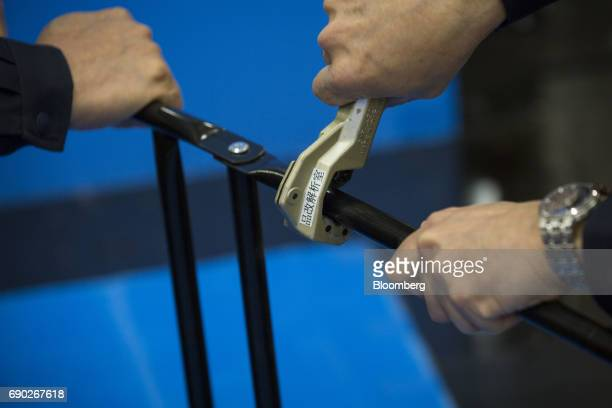 A member of a Nitori Holdings Co quality control team cuts the metal part of a chair to check its width and the thickness of its paint coating during...