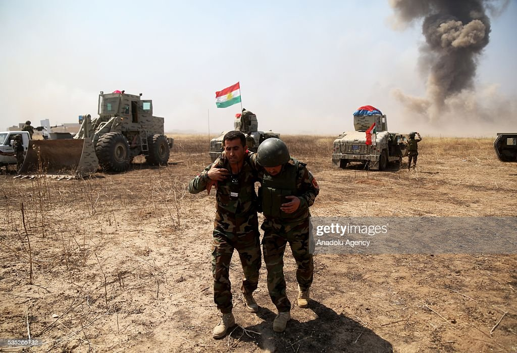 A member of a Peshmerga force carry an injured member as they conduct an operation against Daesh terrorists in Hazer region Mosul, Iraq on May 29, 2016. Coalition forces support the operation with warcrafts.