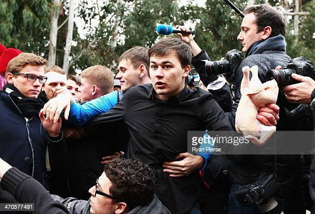A member of a proKremlin youth organization throws a chicken during a press conferance held by protest group Pussy Riot on February 20 2014 in Sochi...