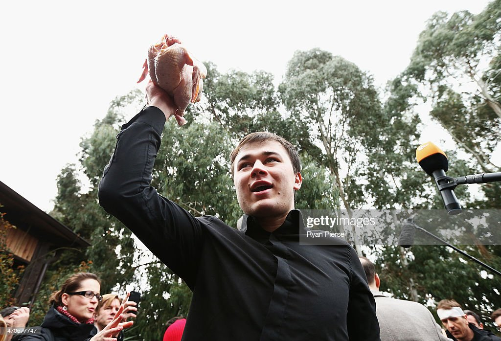 A member of a pro-Kremlin youth organization throws a chicken during a press conferance held by protest group Pussy Riot on February 20, 2014 in Sochi, Russia.